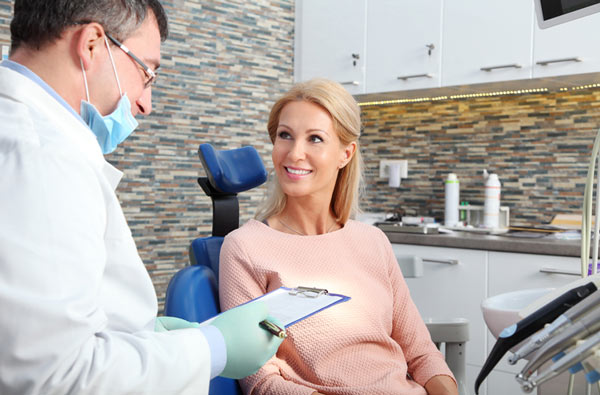 Woman talking to dentist during dental exam at Gregory J. Gorman, DMD in Grand Junction, CO